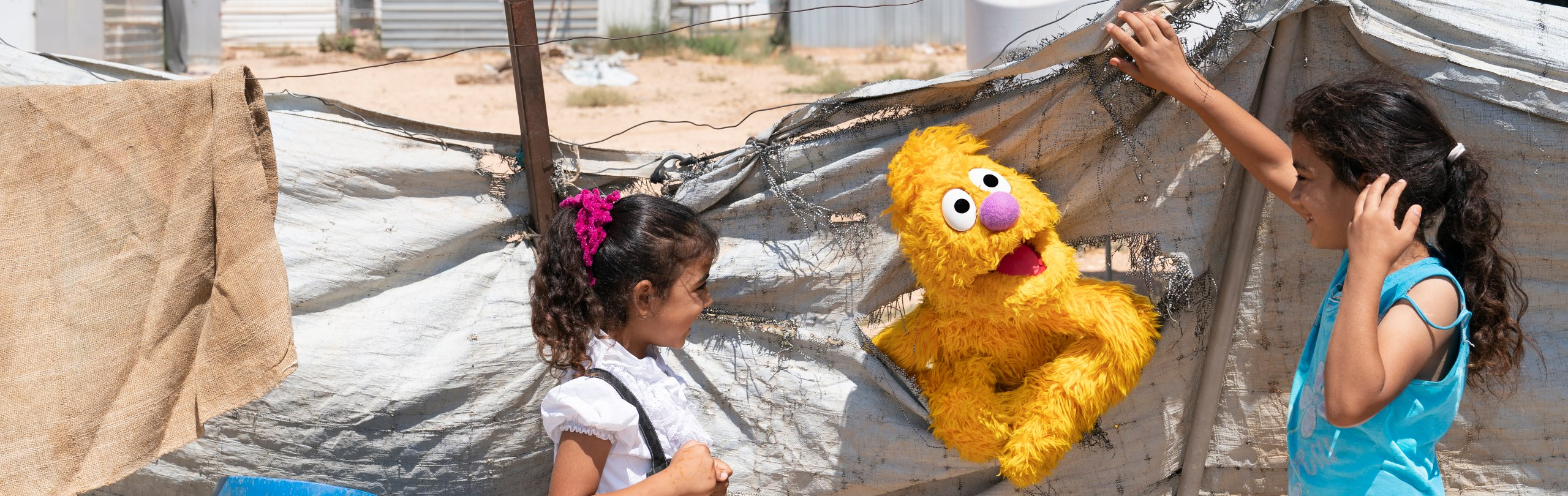Two girls smile with a yellow muppet